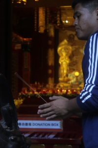 A Buddhist prays at Singapore's Tooth Relic Temple & Museum. Incense is ultimately associated with prayer rituals here.