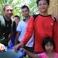 These Balud Batu teenagers and children stand by a basin of rainwater that has fallen from the roof of Roadiah Aling's house. Using this method for household chores will continue to conserve the fresh water from the reservoir being channeled to the tap nearby.