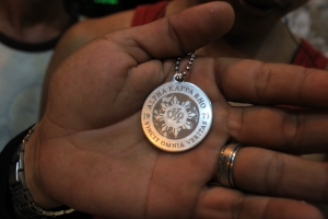 A symbol of brotherhood. A silver medallion necklace of AKP 73, which was heated up and burned into Adz's and other members' arms when they were initiated into the gang-frat.