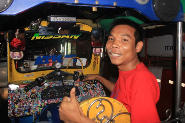 A Bangkok tuk tuk driver gives a big grin after a long drive through the Bangkok streets. Tuk tuks are the primary medium of transport here.