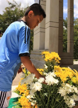 A young man pays respect to the victims of the Killing Fields & lays a bouquet of flowers outside the site's memorial.