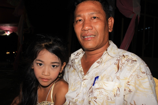 Run proudly smiles for a photo with his youngest daughter, 13, in Phnom Penh.