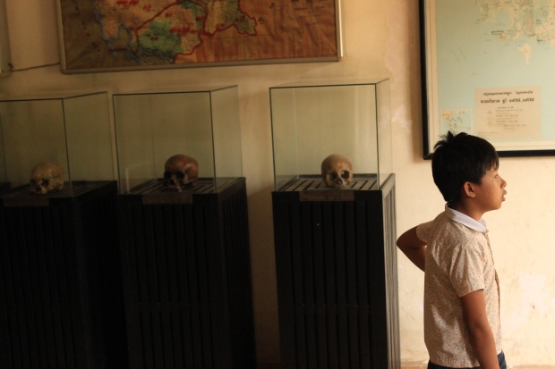 A child visitor walks past exhibit cases with skulls on display at Tuol Sleng.