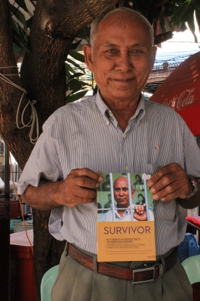One of three living survivors to escape the clutches of Tuol Sleng prison, Chum Mey sells his book at the facility's gates.