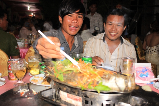 Table guests digging in to a steamed fish dish.