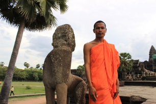 A monk poses beside an ancient lion statue near the entrance to Angkor Wat.