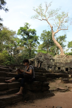 A tourist absorbs a book amidst this treasured jungle backdrop.