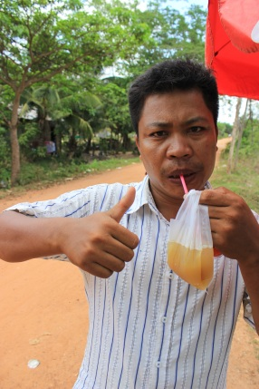 "Lucky shows off the sugar cane drink he just purchased for us on the side of the country following a cruise into the rustic Cambodian countryside on his tuk tuk. After showing Lucky the photo I took of him, he thoughtfully commented on his own portrait, remarking, ""Very handsome."""