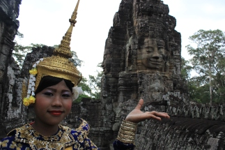A Cambodian woman in traditional dance attire poses in front of the many faces at Angkor Thom.