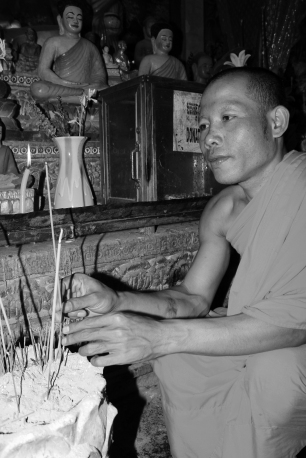 A monk prays & lights incense at a Buddhist temple in Siem Reap.