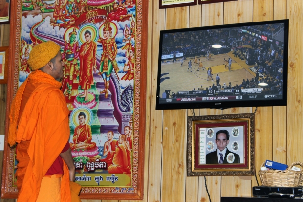 A young Cambodian monk watches a NCAA basketball game before prayers at Wat Jotanaram.